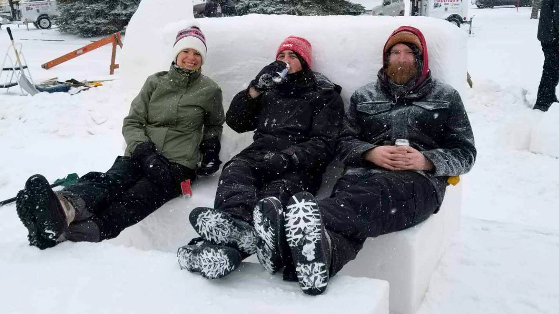 Three people sitting on a couch made of snow